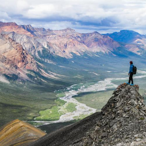 Hiker standing on peak, overlooking valley.